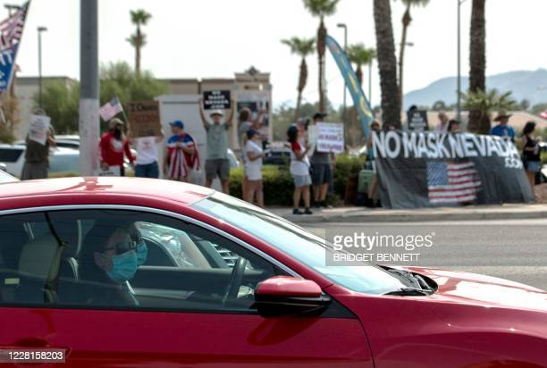 """People wearing masks drive past protestors rallying against a mask mandate in Las Vegas, Nevada on August 22, 2020. - """"On day one"""" of his own..."""