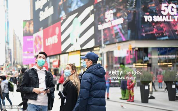 People wearing masks enjoy the sun at Times Square on March 14 2020 in New York City The World Health Organization said March 13 2020 it was not yet...
