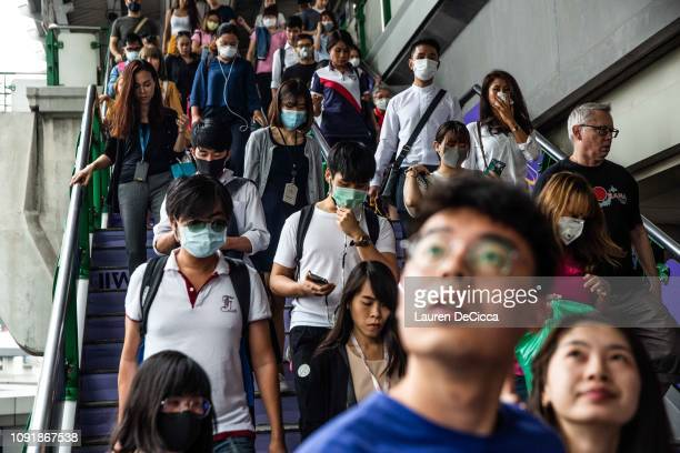 People wearing masks exit the BTS train station at the Asoke intersection on January 31, 2019 in Bangkok, Thailand. The Thai Government has ordered...