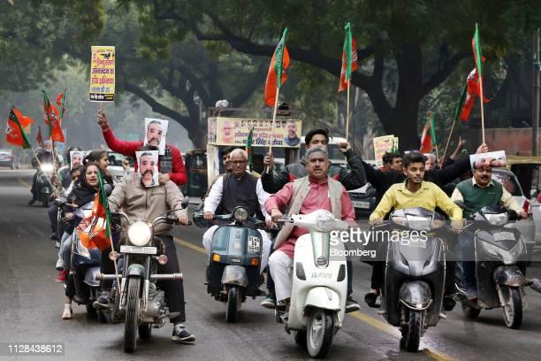 People wearing masks in the likeness of Indian Air Force pilot Abhinandan Varthaman and holding Bharatiya Janata Party flags ride on motorcycles...