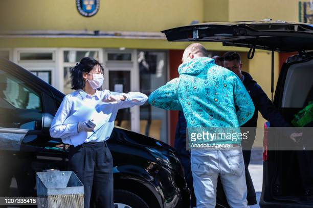 People wearing masks make an elbow bump greeting as a precaution against the coronavirus in Skopje North Macedonia on March 16 2020