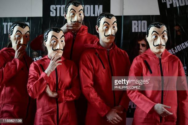 People wearing masks of the Spanish TV show La Casa de Papel arrive to watch the 3rd season on July 15 2019 in Paris