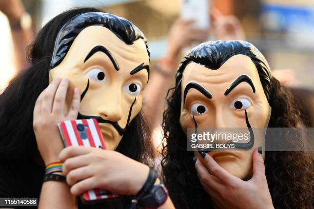 People wearing masks of the Spanish TV show La Casa de Papel pose before a photocall for the presentation of the 3rd season of the show on July 11...