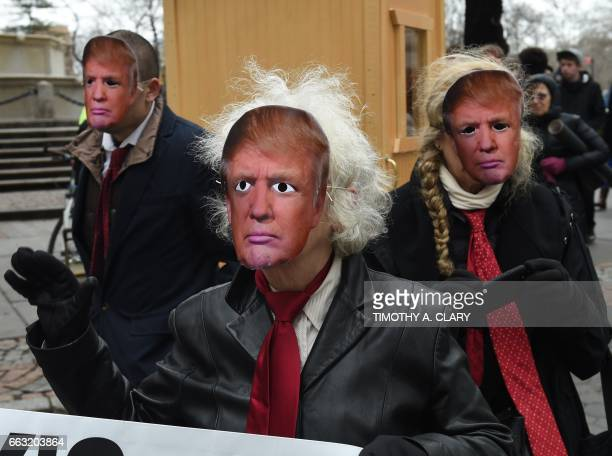 People wearing masks of US President Donald Trump take part in the 32nd Annual April Fools Day Parade in New York on April 1 2017 The theme for this...