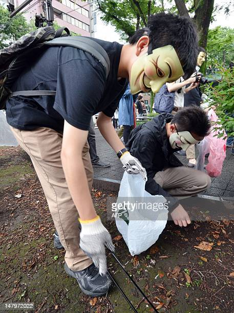 People wearing masks pick up litter as part of a clean up mission organised by hacker collective Anonymous on a street in Tokyo on July 7, 2012....