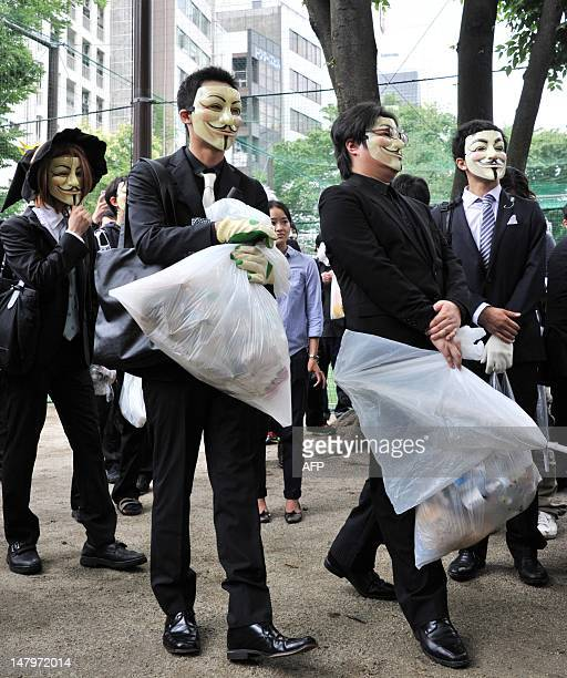 People wearing masks pick up litter as they attend a clean up mission organised by hacker collective Anonymous on a street in Tokyo on July 7, 2012....