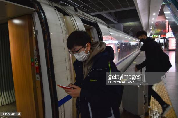 People wearing masks prepare to board a train in the direction of Wuhan City at Hongqioa train station as they head home for the Lunar New Year in...