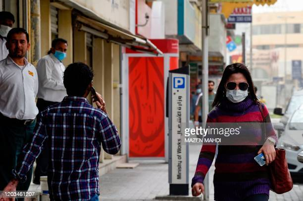 People wearing masks seen in the heart of the Bahraini capital Manama on February 26, 2020. - The first case of novel coronavirus in Bahrain was of a...