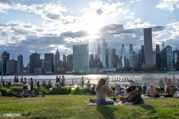 People wearing masks sit at Gantry Plaza State Park, Long Island City with the Manhattan skyline in the background on May 30, 2020 in New York City....