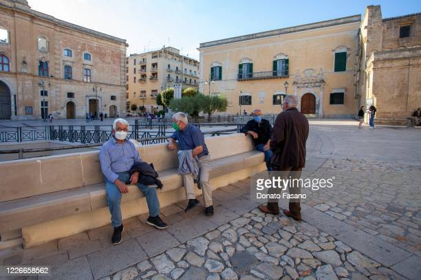 People wearing masks sit at Piazza Vittorio Veneto on May 23 2020 in Matera Italy Restaurants bars cafes hairdressers and other shops have reopened...