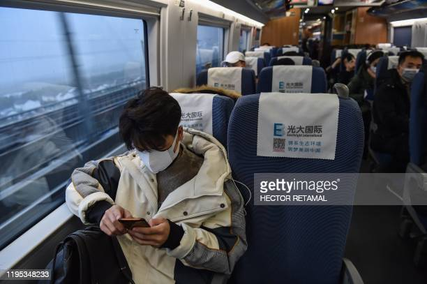 People wearing masks sit in a train for the direction of Wuhan City at Hongqioa train station as they head home for the Lunar New Year in Shanghai on...