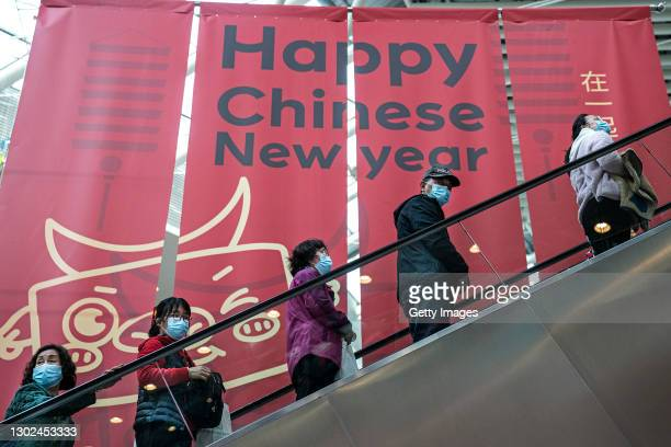 People wearing masks take an escalator past slogans of celebrating the Chinese New Year in Shopping Mall during the fifth day of Spring Festival on...