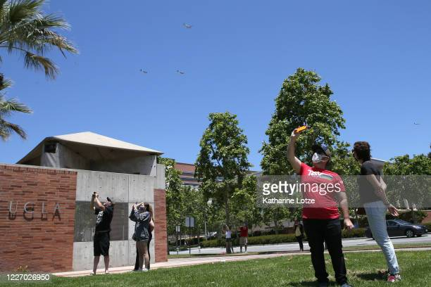 People wearing masks take photos as historic planes fly over the UCLA Medical Center in honor of Memorial Day on May 25 2020 in Westwood California...