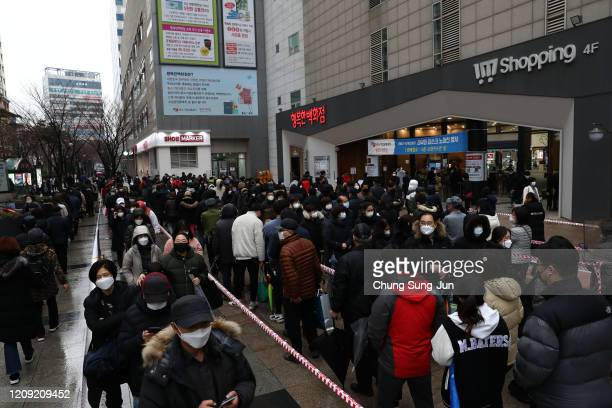People wearing masks to prevent the coronavirus line up to buy face masks at a department store on February 28 2020 in Seoul South Korea Government...