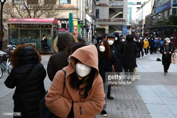 People wearing masks to prevent the coronavirus line up to buy face masks at a department store on March 02 2020 in Seoul South Korea The South...