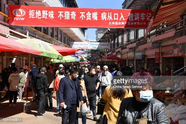 People wearing masks visit a market amid the coronavirus outbreak on March 8, 2020 in Kunming, Yunnan Province of China.