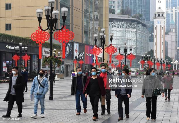 People wearing masks visit Jiefangbei pedestrian street amid the coronavirus outbreak on March 13 2020 in Chongqing China