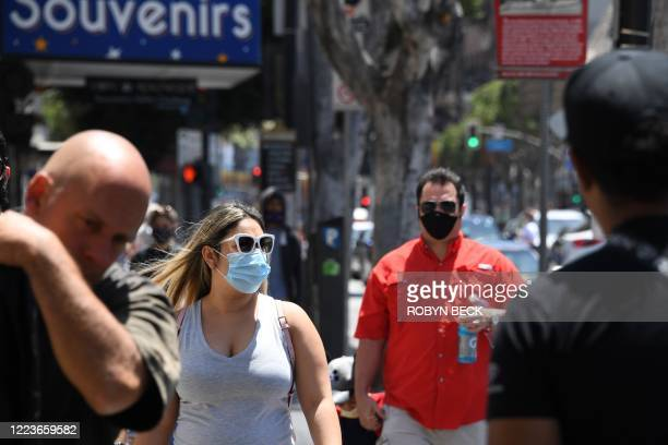 People wearing masks visit the Hollywood Walk of Fame in Hollywood, California June 30, 2020. - Due to a spike in coronavirus cases California Gov....