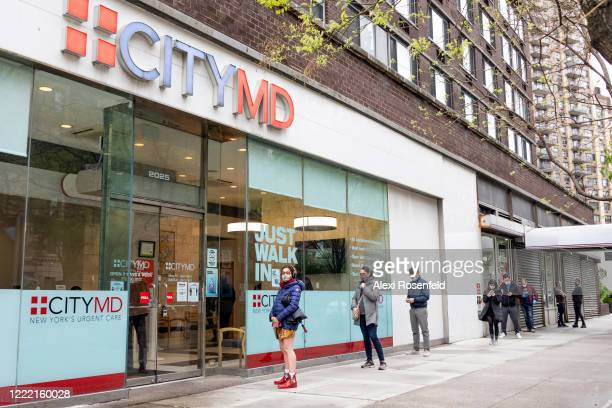 People wearing masks wait in line outside a CityMD location to be tested for coronavirus on April 30 2020 in New York City United States On April...