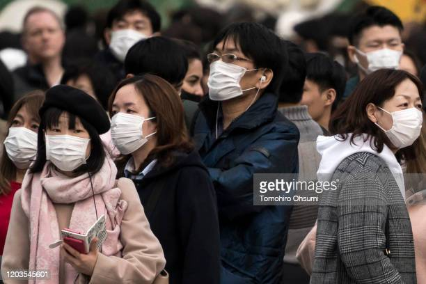 People wearing masks wait to cross a road in the Shibuya district on February 02 2020 in Tokyo Japan Japan reported 20 cases of Wuhan coronavirus...