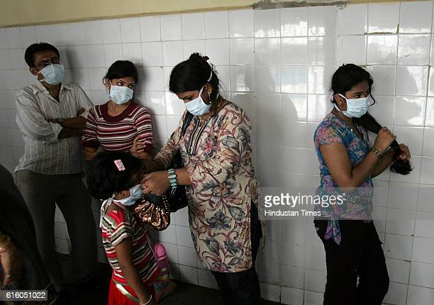 People wearing masks wait to get tested for H1N1 influenza at a special ward in Kasturba Hospital in Mumbai