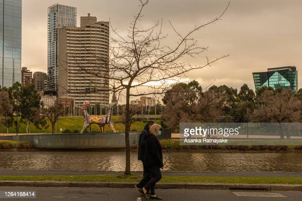 People wearing masks walk along the banks of the Yarra River on August 06 2020 in Melbourne Australia Under current restrictions people are allowed...