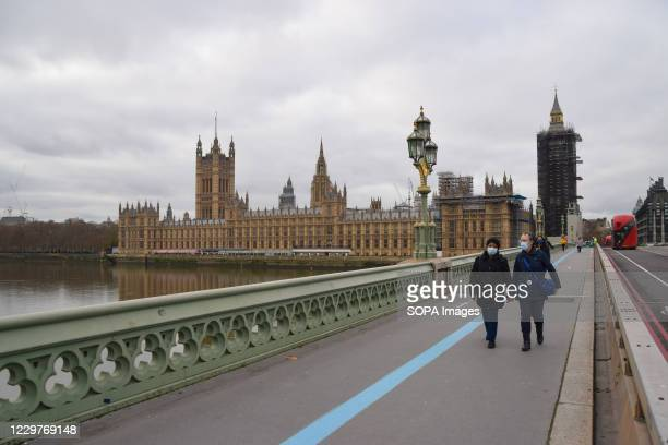 People wearing masks walk along the Westminster Bridge. The UK government has announced a new coronavirus tier system for England while restrictions...