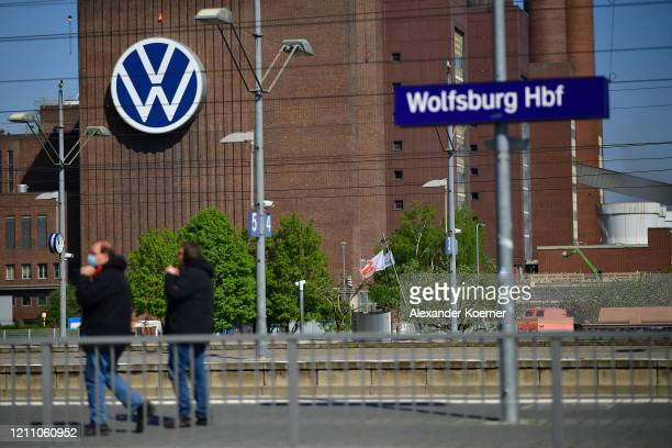 People wearing masks walk by the Volkswagen factory during the coronavirus crisis on April 27, 2020 in Wolfsburg, Germany. Production was shut down...