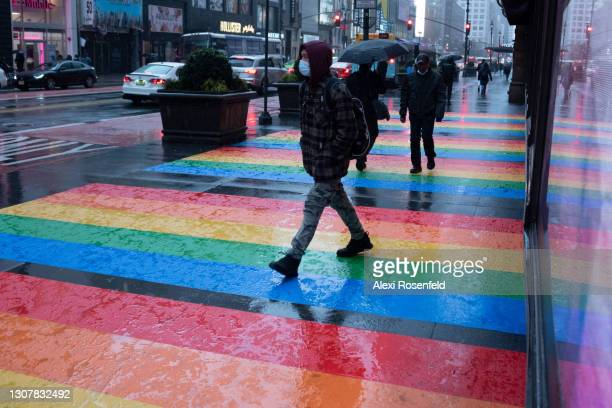 People wearing masks walk in the rain across a rainbow colored sidewalk part of Lacoste's window display at Macy's Herald Square on March 18, 2021 in...