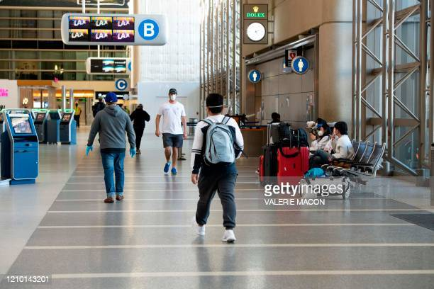 People wearing masks walk inside Tom Bradley Terminal at Los Angeles International Airport during the outbreak of the novel coronavirus which causes...