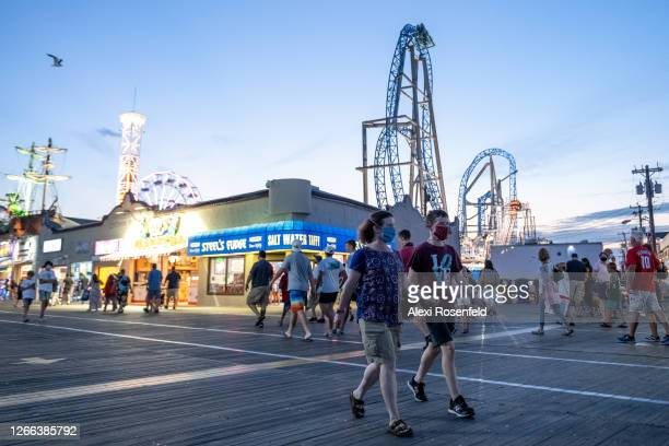 People wearing masks walk on the boardwalk with a rollercoaster in the background at twilight as the state of New Jersey continues Stage 2 of...