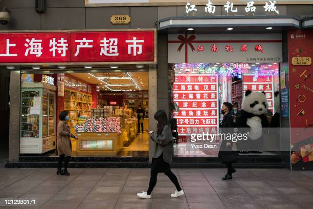People wearing masks walk past a store with a clerk dressing as a Panda at Nanjing road commercial area on March 17, 2020 in Shanghai, China. Health...