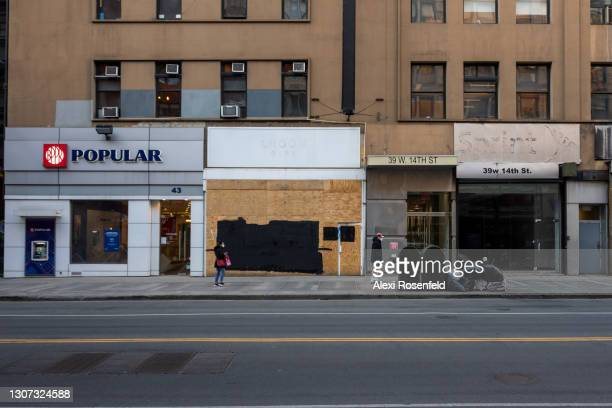 People wearing masks walk past closed down retail stores on March 15, 2021 in New York City. After undergoing various shutdown orders for the past 12...