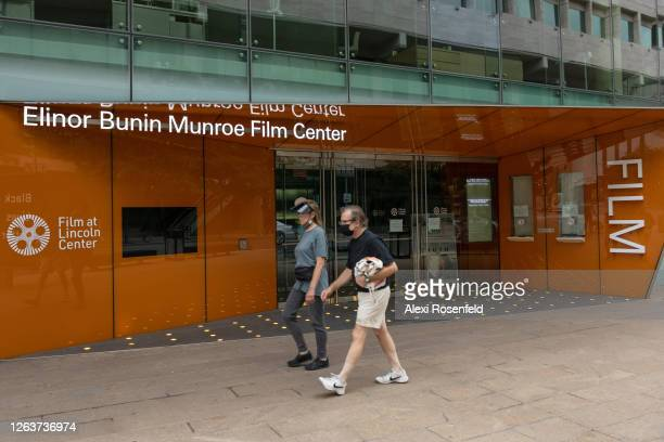 People wearing masks walk past the Elinor Bunin Munroe Film Center at the Lincoln Center for the Performing Arts as the city continues Phase 4 of...