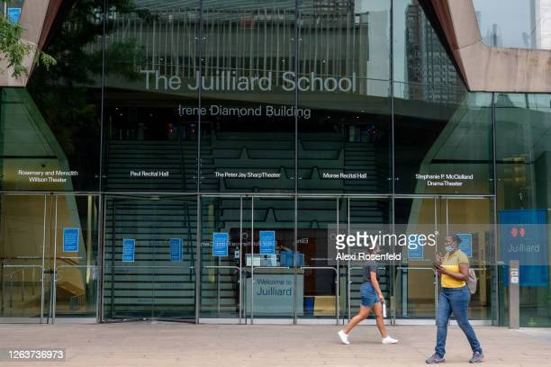 People wearing masks walk past the Irene Diamond Building at The Juilliard School as the city continues Phase 4 of reopening following restrictions...