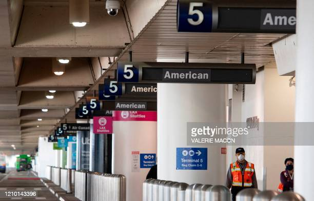 People wearing masks walk through Terminal 5 under American Airlines signs at Los Angeles International Airport during the outbreak of the novel...