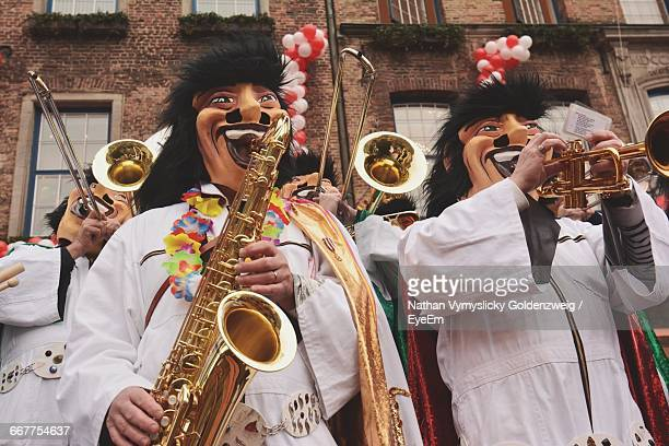 People Wearing Masks While Playing Saxophone And Trumpet During Carnival