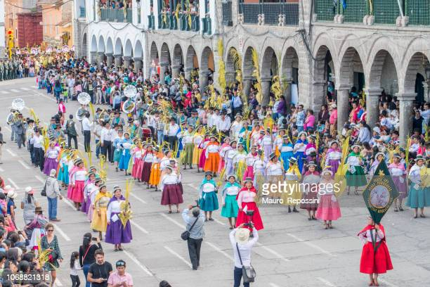 People wearing multicolored dresses and hats and a marching band during the celebration of the Palm Sunday of Easter at Ayacucho city, Peru.