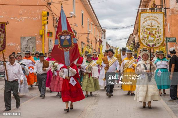 People wearing multicolored dresses and hats marching during the celebration of the Palm Sunday of Easter at Ayacucho city, Peru.