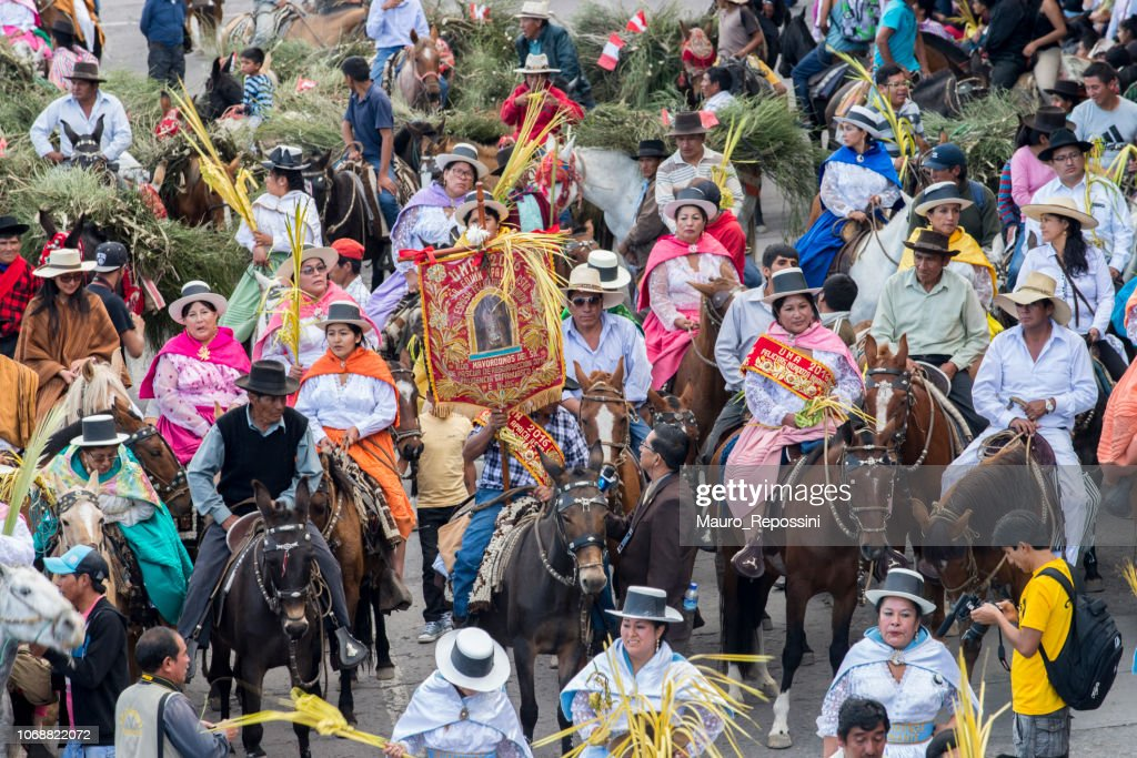 People wearing multicolored dresses and hats riding on horses during the celebration of the Palm Sunday of Easter : Stock Photo