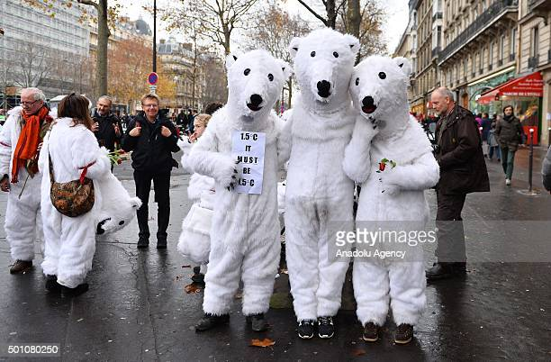 People wearing polar bear costumes are seen while activists stage a demonstration near the Arc de Triomphe at the Avenue de la Grande Armee boulevard...