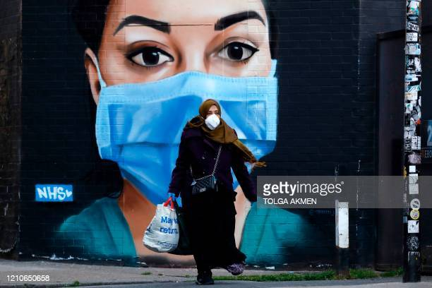 People wearing PPE as a precautionary measure against COVID19 walk past a mural of an NHS worker in central London as Britain remains under lockdown...