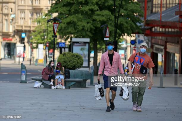 People wearing PPE , including a face mask as a precautionary measure against COVID-19, carry shopping bags as they walk along an almost empty street...