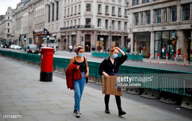 People wearing PPE , including face masks as a precautionary measure against COVID-19, use a pavement, recently widened to accomodate social...