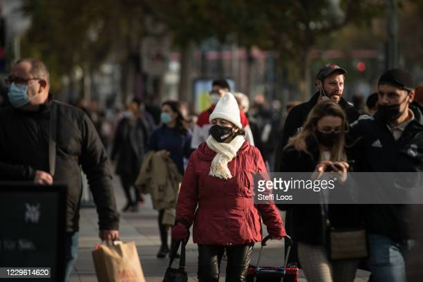 People wearing protective face masks and shopping bags walk down a shopping street under a four-week semi-lockdown during the second wave of the...