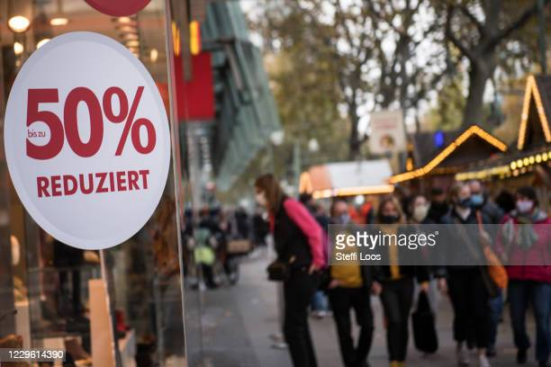 People wearing protective face masks and shopping bags walk past a shop window with the sign Sale on a shopping street under a four-week...