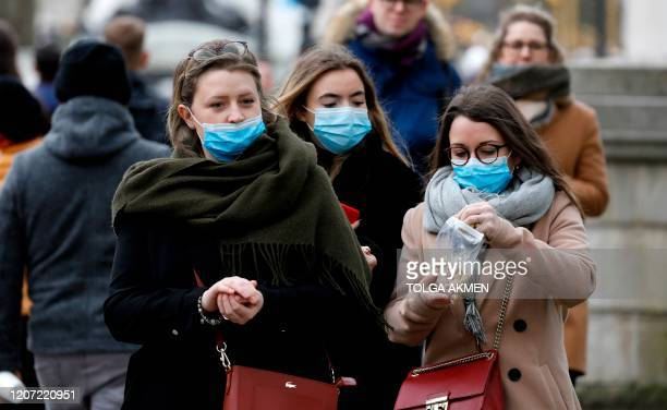 People wearing protective face masks are pictured near to Buckingham Palace in central London on March 15 2020
