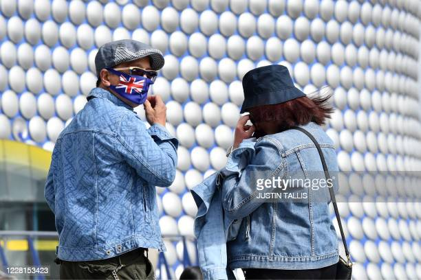 People wearing protective face masks are seen outside the Bullring shopping centre in Birmingham, central England on August 22 as Britain's...