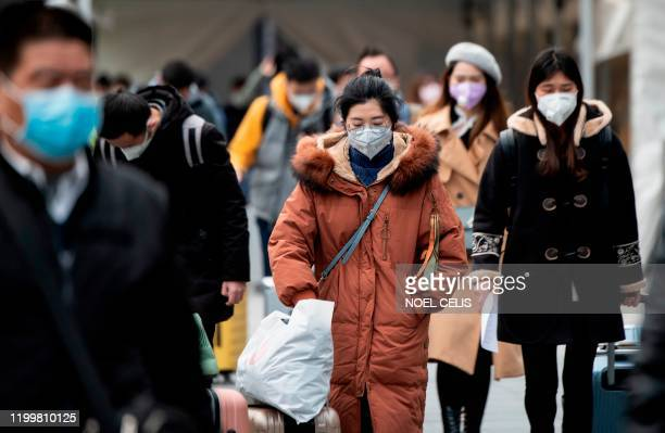 People wearing protective face masks arrive at a railway station in Shanghai on February 10, 2020. - The death toll from the novel coronavirus surged...