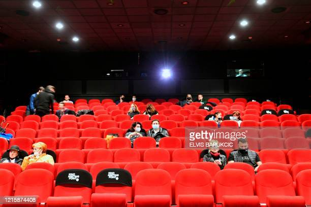 "People wearing protective face masks await the beginning of the first movie show at Sarajevo's ""Meeting Point"" cinema, on May 28 after a two-month..."
